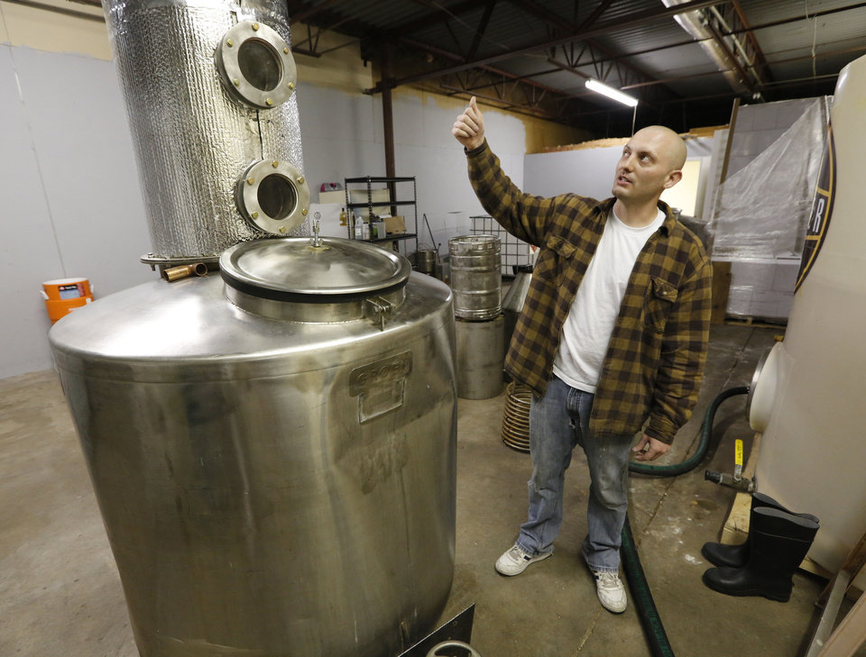 Photo - Twister Distillery owner Garrett Janko explains how to distill spirits in Moore. Photo by Steve Gooch, The Oklahoman