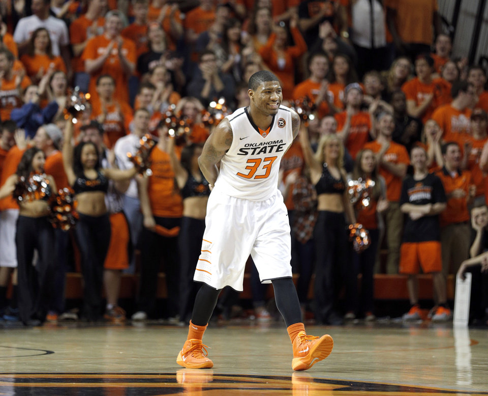 Photo - Oklahoma State's Marcus Smart (33) smiles after a Cowboy score during the men's college basketball game between Oklahoma State and Texas Tech at Gallagher-Iba Arena in Stillwater, Okla., Saturday, Feb. 22, 2014. OSU won 84-62. 