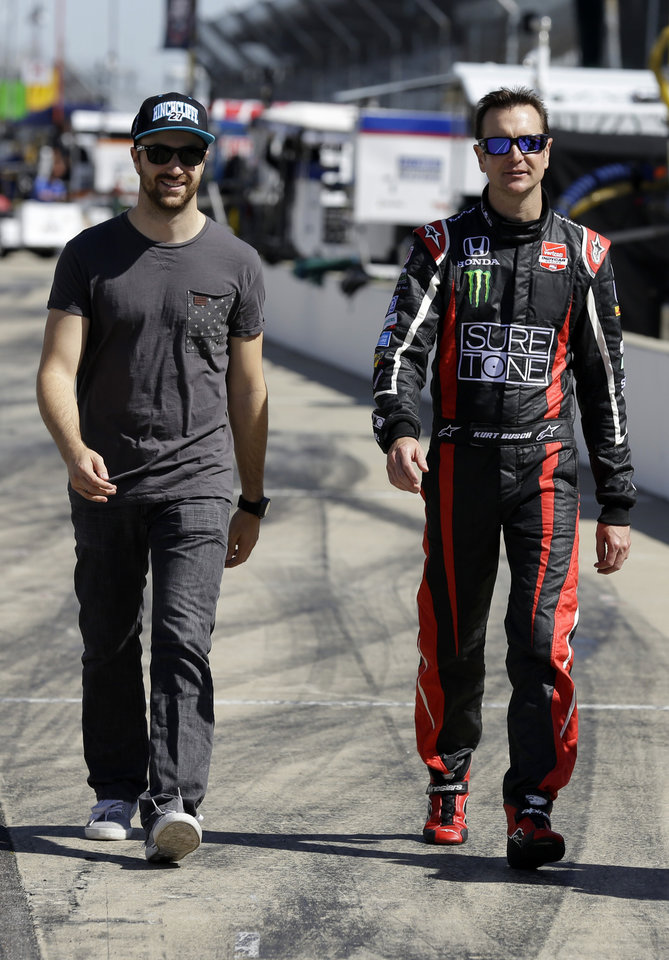 Photo - Race driver Kurt Busch, right, walks with teammate James Hinchcliffe, of Canada, before the start of practice at the Indianapolis Motor Speedway during the Rookie Orientation Program in Indianapolis, Tuesday, April 29, 2014. Busch will try to be the first driver in a decade to compete in IndyCar's Indianapolis 500 auto race and Sprint Cup's Coca-Cola 600 on the same day. (AP Photo/Michael Conroy)