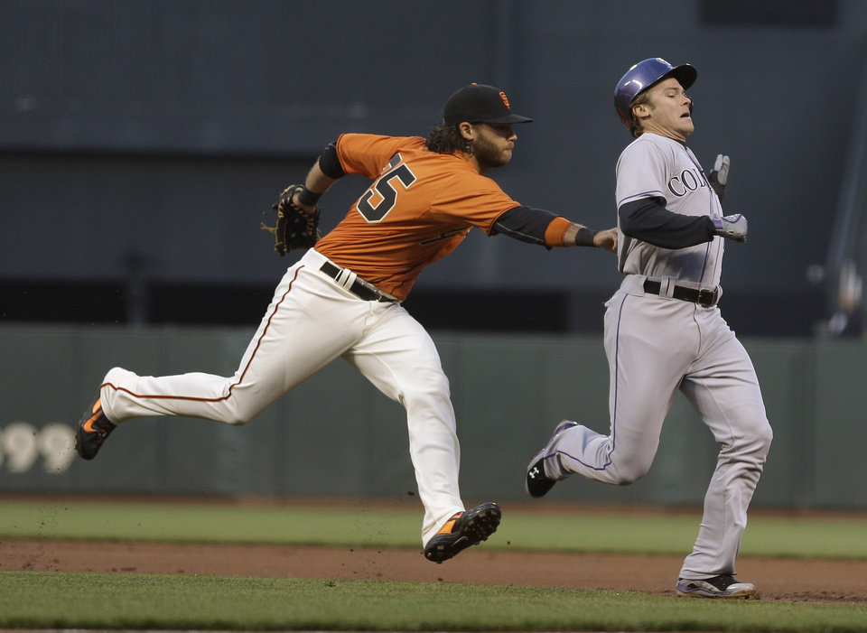 Photo - San Francisco Giants shortstop Brandon Crawford, left, tags out Colorado Rockies' Josh Rutledge, right, who was trying to steal second base during the first inning of a baseball game Friday, April 11, 2014, in San Francisco. The Rockie's Brandon Barnes scored from third base on the play. (AP Photo/Eric Risberg)