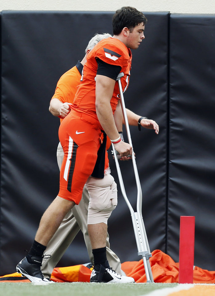 Photo - OSU quarterback Wes Lunt (11) leaves the field on crutches after being injured in the first quarter during a college football game between Oklahoma State University and the University of Louisiana-Lafayette (ULL) at Boone Pickens Stadium in Stillwater, Okla., Saturday, Sept. 15, 2012. Photo by Nate Billings, The Oklahoman