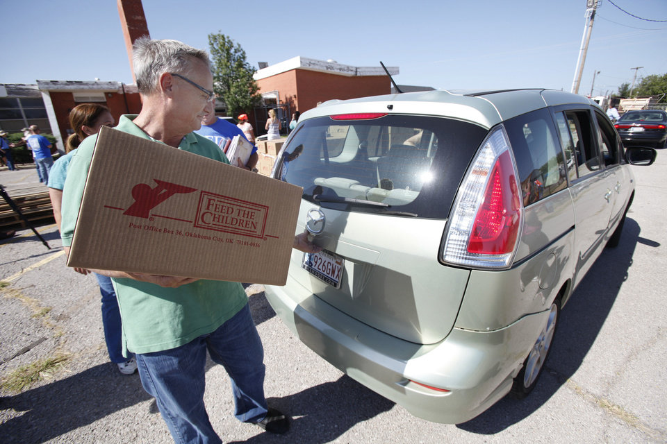 Volunteer Steve Eaton loads a car during a joint food drive with Feed The Children and Mustard Seed Development Corporation   in Oklahoma City, Tuesday 25, 2012. Photo By Steve Gooch, The Oklahoman