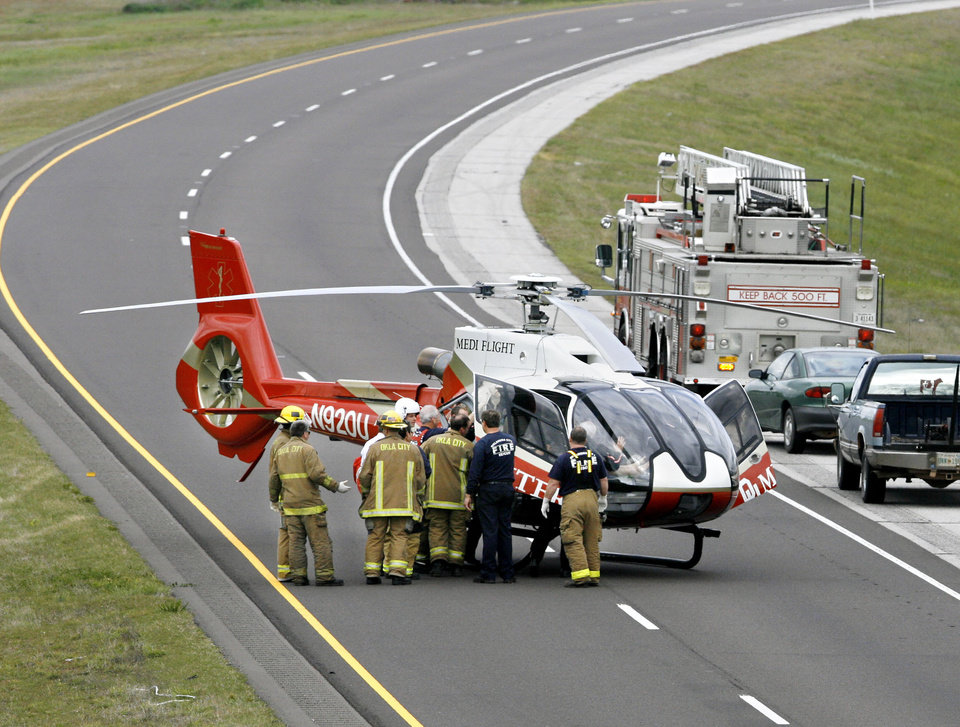 Oklahoma City firefighters assist Mediflight helicopter personnel loading an accident victim at the scene of an automobile accident  Wednesday around 4:30 pm,   April 18, 2007.  Eastbound traffic on Interstate 40 was blocked briefly while the helicopter landed on the highway near Westminster. By Jim Beckel,  The Oklahoman.