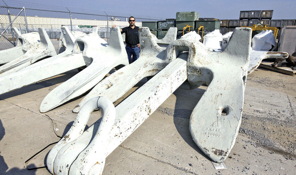 Government Liquidation warehouse Director Stephen Jackson stands beside the Navy ship anchors being sold at auction. They weigh 35,000 pounds each, are 16.7 feet long, 13 feet wide and made of steel. <strong>PAUL HELLSTERN - The Oklahoman</strong>