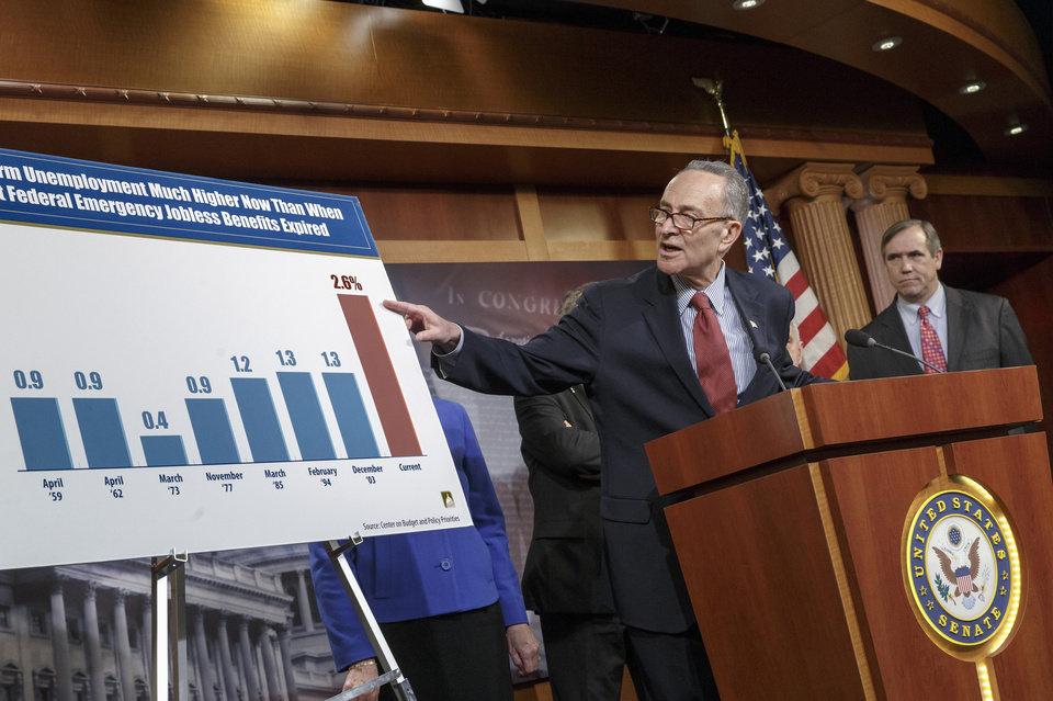 Photo - Sen. Charles Schumer, D-N.Y., left, accompanied by Sen. Jeff Merkley, D-Ore., meets with reporters on Capitol Hill in Washington, Tuesday, Jan. 7, 2014, after legislation to renew jobless benefits for the long-term unemployed unexpectedly cleared an initial Senate hurdle. The vote was 60-37 to limit debate on the legislation, with a half-dozen Republicans siding with the Democrats on the test vote. Sen. Jack Reed, D-R.I., along with Republican Sen. Dean Heller of Nevada, led the effort to reauthorize the benefits for three months which expired on Dec. 28. (AP Photo/J. Scott Applewhite)