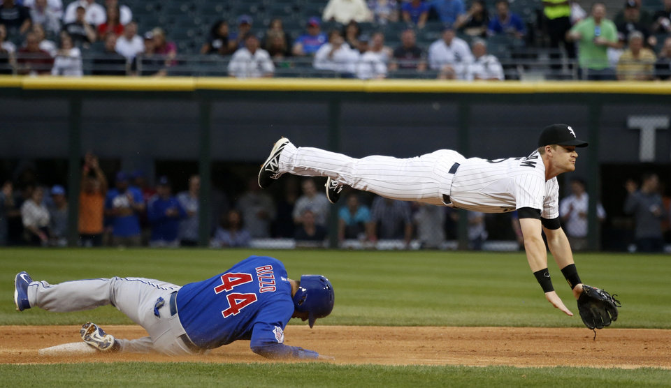 Photo - Chicago White Sox second baseman Gordon Beckham, right, turns the double play getting Chicago Cubs' Anthony Rizzo at second and Starlin Castro at first, during the first inning of an interleague baseball game Thursday, May 8, 2014, in Chicago. (AP Photo/Charles Rex Arbogast)