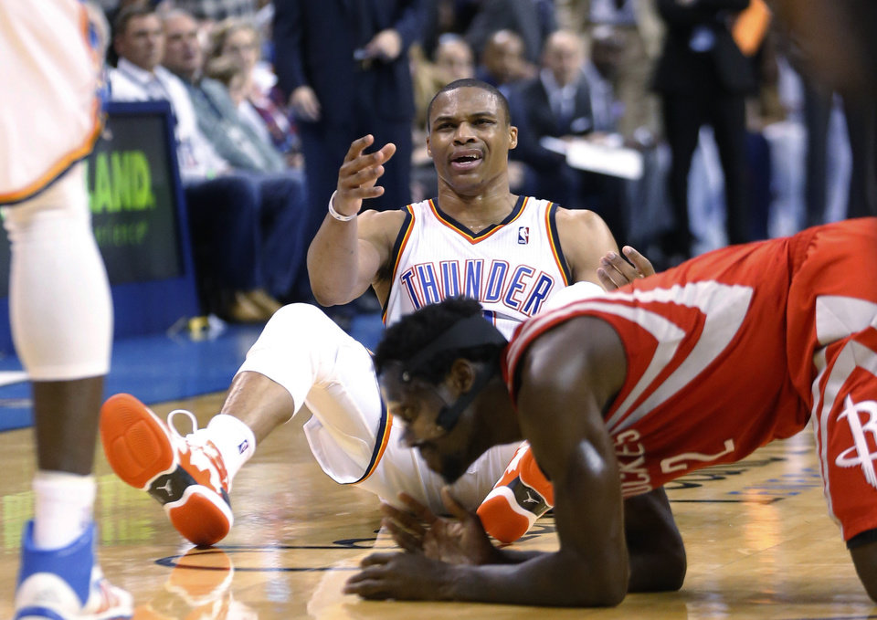 Photo - Oklahoma City Thunder guard Russell Westbrook (0) reacts after a foul by Houston Rockets guard Pat Beverley, right, during the fourth quarter of an NBA basketball game in Oklahoma City, Tuesday, March 11, 2014. Oklahoma City won 106-98. (AP Photo/Sue Ogrocki)