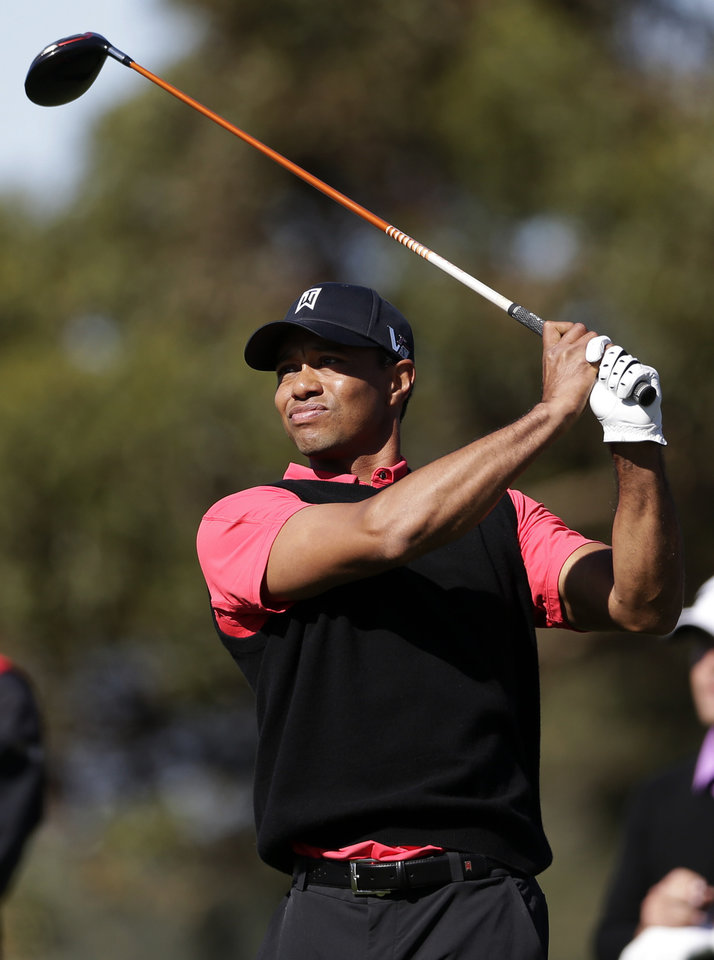 Photo - Tiger Woods watches his tee shot on the 10th hole during the fourth round of the Farmers Insurance Open golf tournament at the Torrey Pines Golf Course, Monday, Jan. 28, 2013, in San Diego. (AP Photo/Gregory Bull)