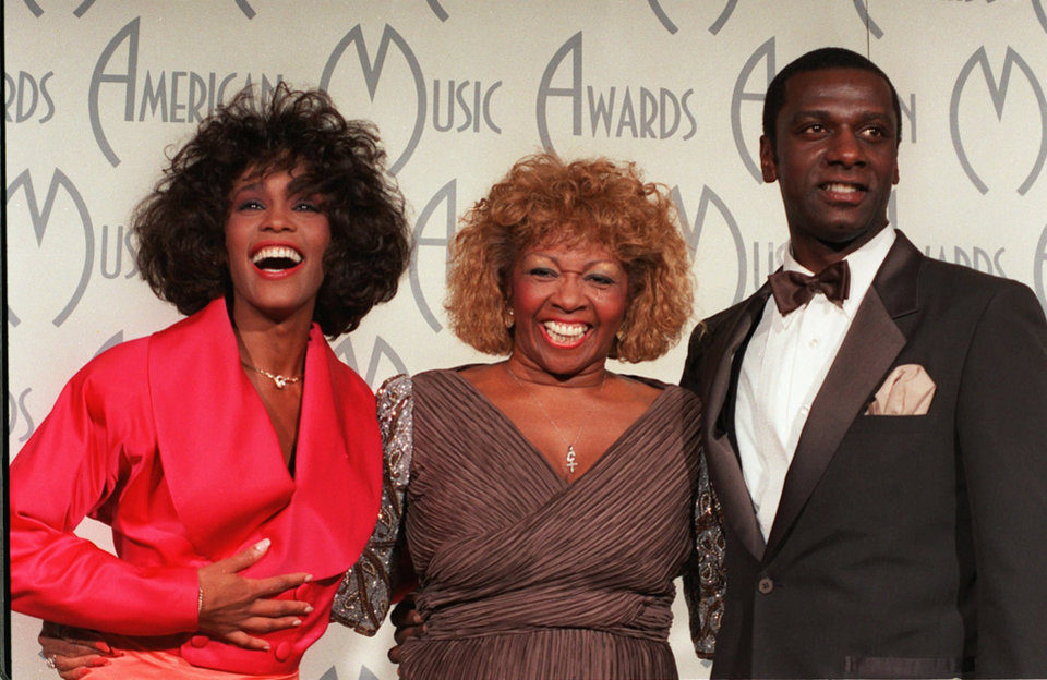FILE - In this Jan. 26, 1998 file photo, singer Whitney Houston, left, celebrates her win at the American Music Awards with her mother, Cissy, and brother, Gary, at the Shrine Auditorium, in Los Angeles. Whitney Houston, who reigned as pop music's queen until her majestic voice and regal image were ravaged by drug use, has died, Saturday, Feb. 11, 2012. She was 48. (AP photo/Reed Saxon, File) ORG XMIT: NY134