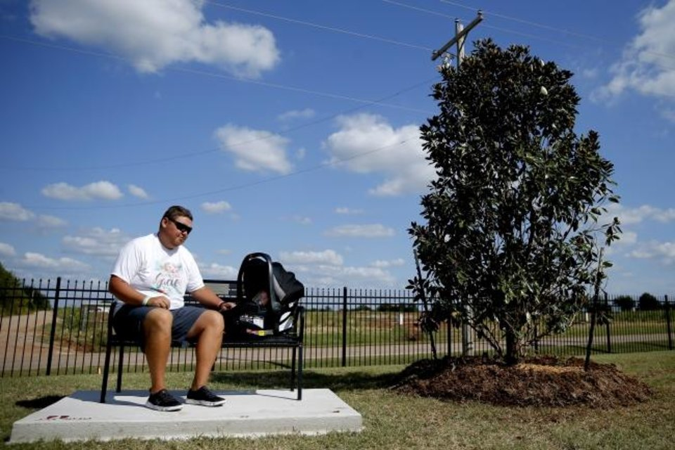 Photo -  Cashion assistant coach Cale Cochran and his son Jaxon listen to music while sitting on a bench dedicated to his late wife Jacie Cochran before a game earlier this season. Jacie died in July during childbirth. She was 26.  [Bryan Terry/The Oklahoman]