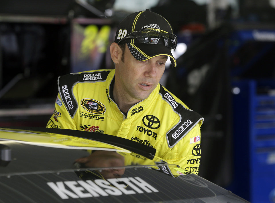 Photo - NASCAR Sprint Cup Series driver Matt Kenseth climbs into his race car in garage area at Pocono Raceway during practice for Sunday's NASCAR Sprint Cup Series auto race in Long Pond, Pa., Friday, June 6, 2014. (AP Photo/Mel Evans)