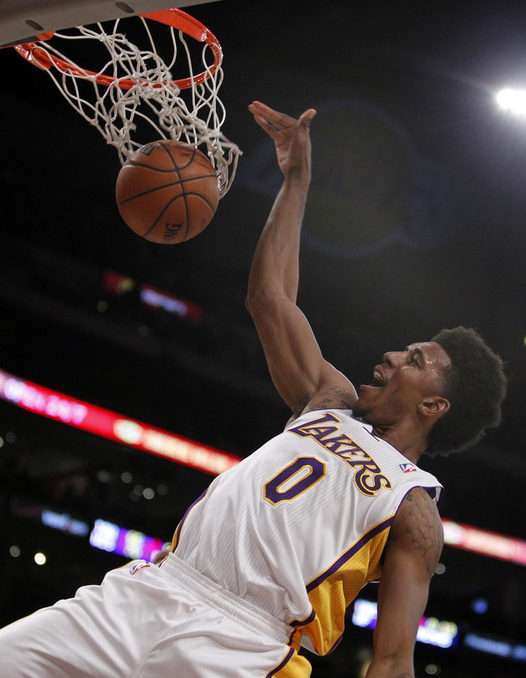 Photo - Los Angeles Lakers forward Nick Young (0) dunks against the Denver Nuggets during the first half of an NBA basketball game Sunday, Jan. 5, 2014, in Los Angeles. (AP Photo/Alex Gallardo)