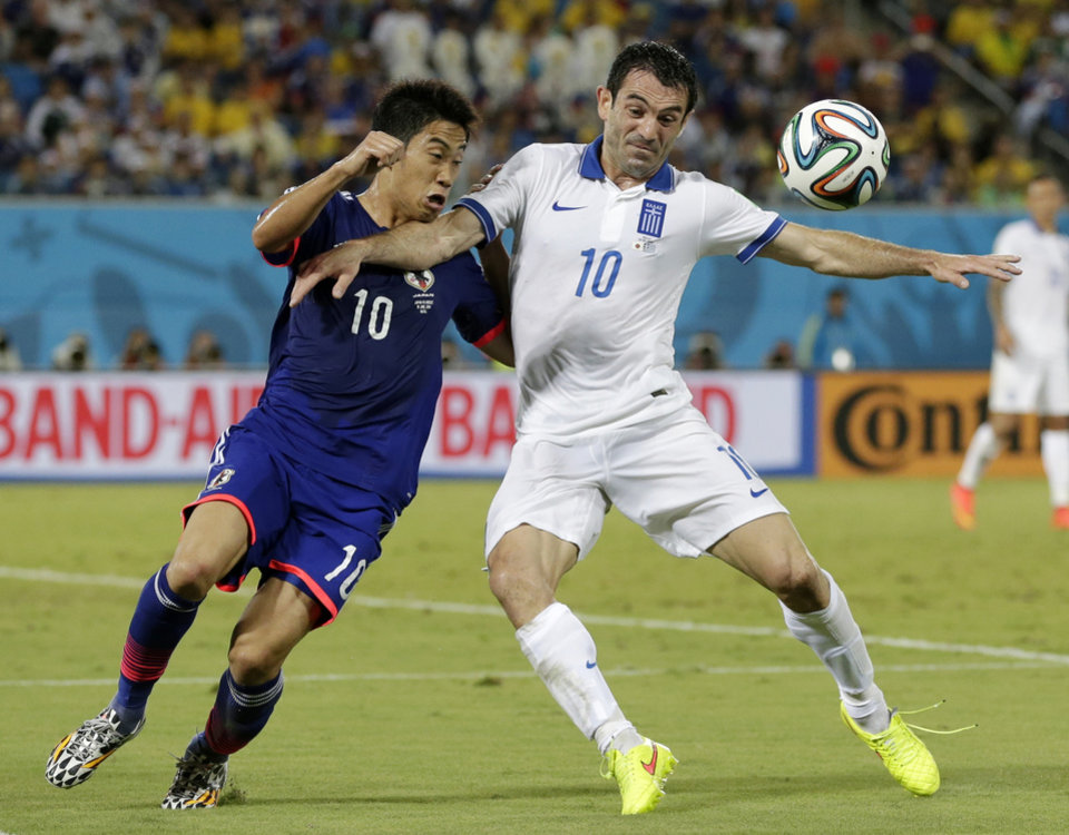 Photo - Greece's Giorgos Karagounis, right, struggles with Japan's Shinji Kagawa to get to the ball during the group C World Cup soccer match between Japan and Greece at the Arena das Dunas in Natal, Brazil, Thursday, June 19, 2014.  (AP Photo/Petr David Josek)