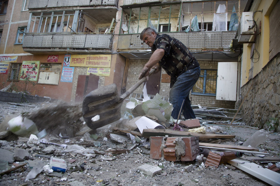Photo - A man removes debris from his house after shelling in the city of Kramatorsk, Donetsk region, eastern Ukraine, Thursday, July 3, 2014. Residential areas came under shelling on Thursday from government forces. (AP Photo/Dmitry Lovetsky)