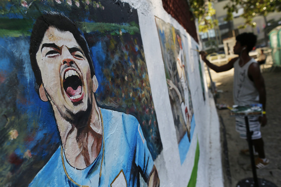 Photo - A mural of Uruguay's soccer striker Luis Suarez covers a wall as artist Marcos Jambeiro paints other players at Copacabana beach in Rio de Janeiro, Brazil, Thursday, June 26, 2014. FIFA banned Suarez from all football activities for four months on Thursday for biting an opponent at the World Cup, a punishment that rules him out of the rest of the tournament. (AP Photo/Leo Correa)