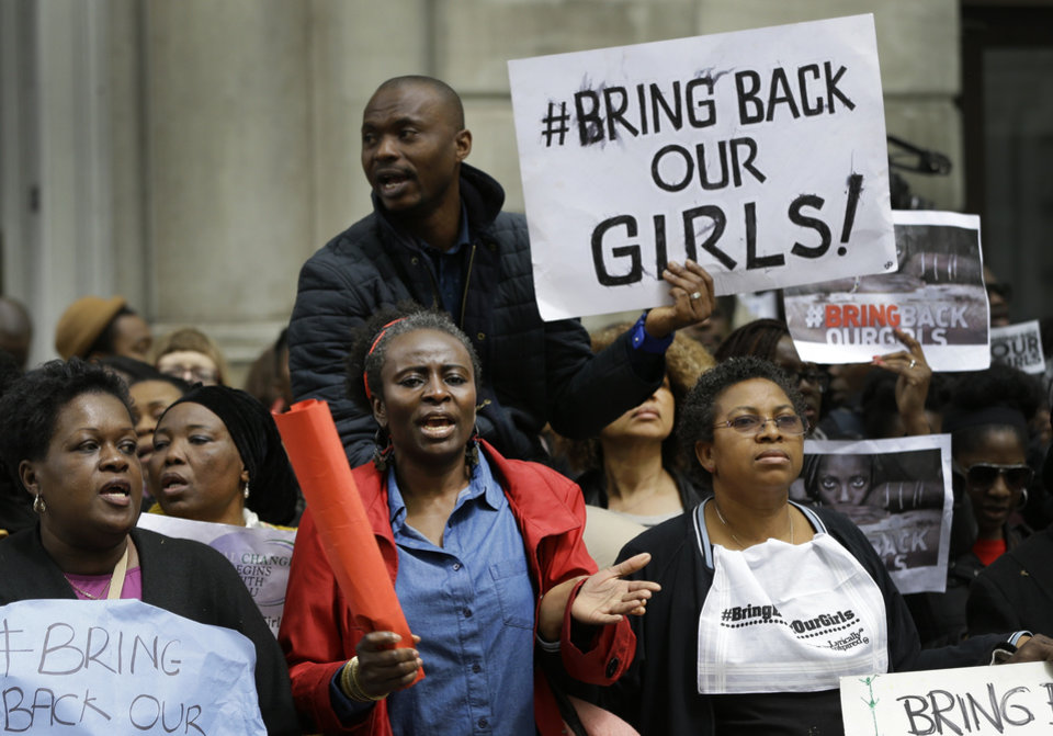 Photo - Demonstrators hold banners as they protest about the kidnapping of girls in Nigeria, near the Nigerian High Commission in London, Friday, May 9, 2014. British experts arrived in the Nigerian capital on Friday to help find at least 276 girls being held by Islamic militants in northeastern Nigeria as an international effort began taking hold. (AP Photo/Kirsty Wigglesworth)