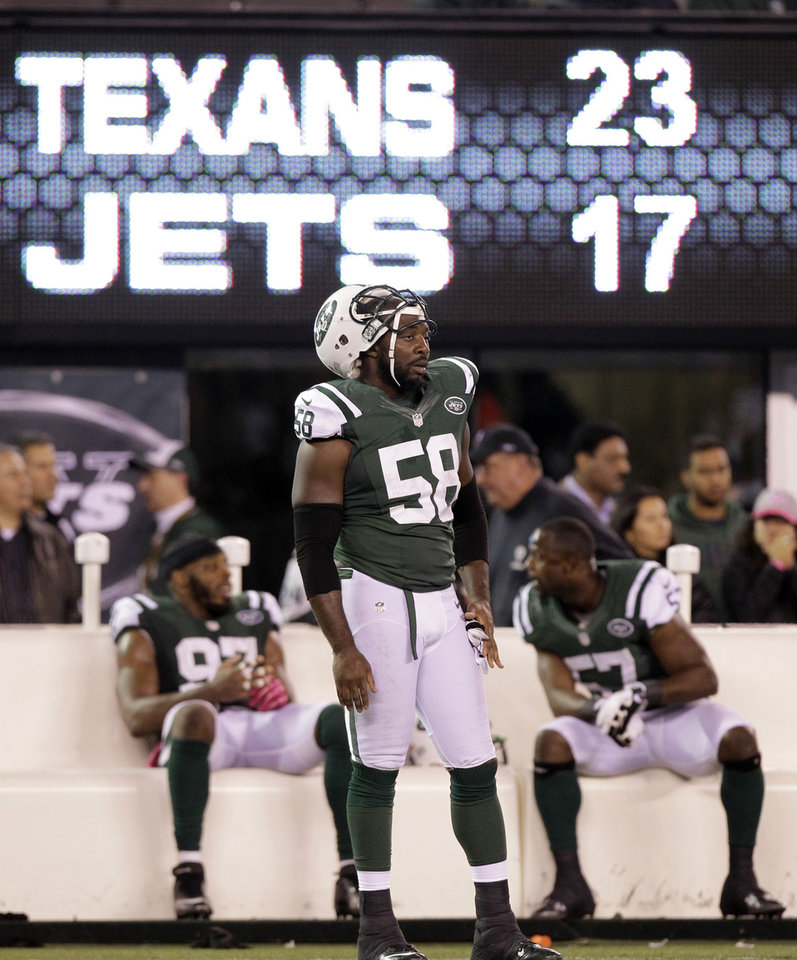 In this photo taken Monday, Oct. 8, 2012, New York Jets' Bryan Thomas (58) and teammates Bart Scott (57) and Calvin Pace (97) watch from the sidelines late in the second half of their 23-17 loss to the Houston Texans in an NFL football game in East Rutherford, N.J. Some of the Jets' biggest flaws were on full display in their loss to the Texans. They couldn't run, the defense couldn't stop the run and Tebow still isn't getting on the field much. (AP Photo/Kathy Willens, File)