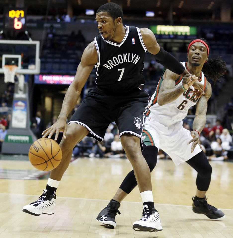 Brooklyn Nets' Joe Johnson (7) drives past Milwaukee Bucks' Marquis Daniels (6) during the first half of an NBA basketball game, Wednesday, Dec. 26, 2012, in Milwaukee. (AP Photo/Morry Gash)