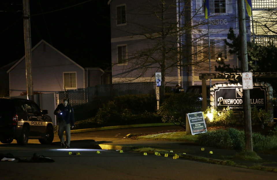 Photo - A police officer walks near evidence markers placed at the scene of an overnight shooting that left five people dead, Monday, April 22, 2013, at the Pinewood Village apartment complex in Federal Way, Wash. (AP Photo/Ted S. Warren)