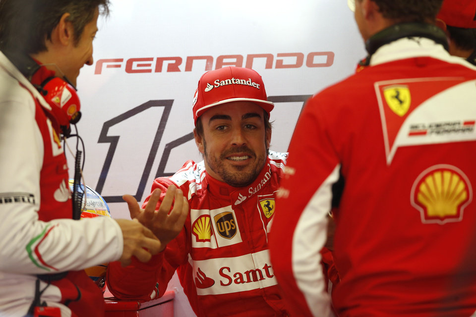 Photo - Ferrari driver Fernando Alonso of Spain talks with mechanics  the pit during the first free practice at the Spa-Francorchamps circuit, Belgium, Friday, Aug. 22, 2014. The Belgium Formula One Grand Prix will be held on Sunday. (AP Photo/Luca Bruno)