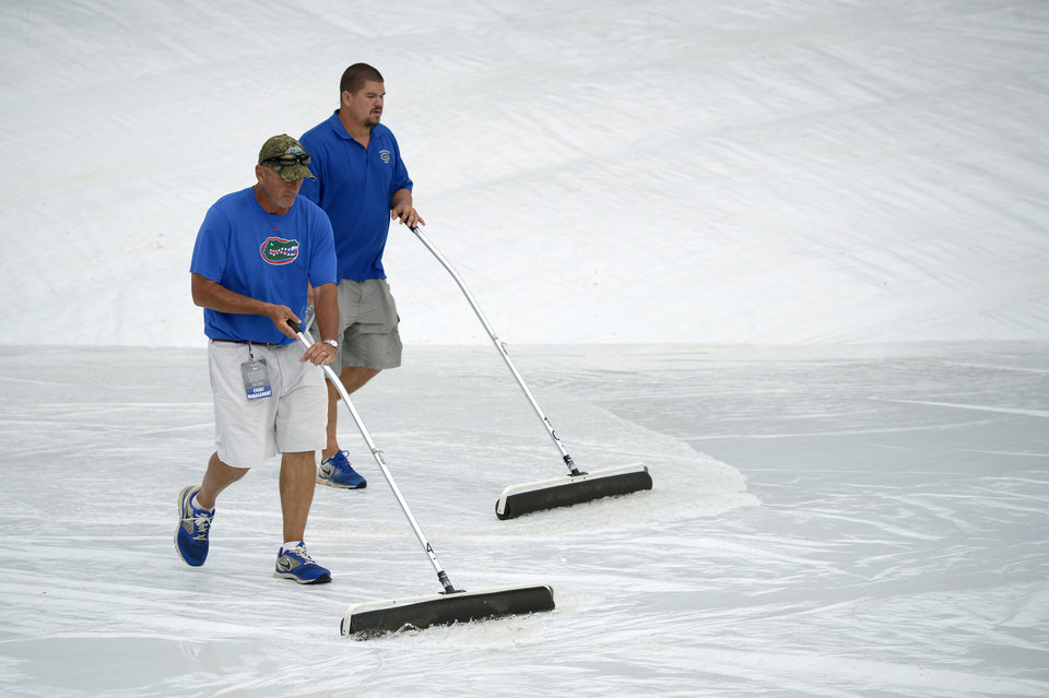 Photo - Members of the grounds crew use squeegees to remove water off the infield tarp during a rain delay in the fourth inning of an NCAA college baseball regional tournament game between Long Beach State and North Carolina in Gainesville, Fla., Sunday, June 1, 2014. (AP Photo/Phelan M. Ebenhack)