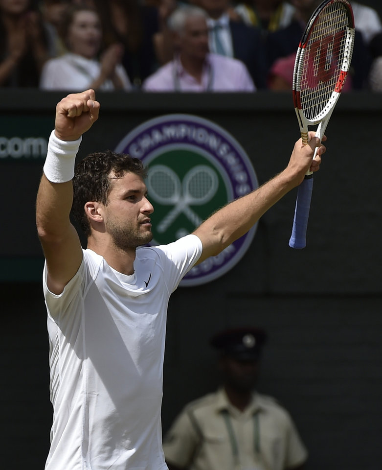 Photo - Grigor Dimitrov of Bulgaria celebrates defeating defending champion Andy Murray of Britain in the men's singles quarterfinal match at the All England Lawn Tennis Championships in Wimbledon, London, Wednesday July 2, 2014. (AP Photo/Toby Melville, Pool)