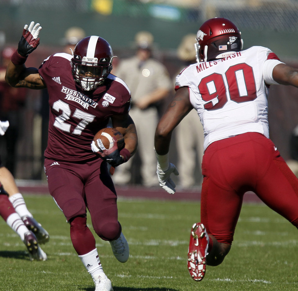 Photo -   Mississippi State running back LaDarius Perkins (27) runs for a short gain past Arkansas defensive end Colton Miles-Nash (90) in the first quarter of their NCAA college football game in Starkville, Miss., Saturday, Nov. 17, 2012. (AP Photo/Rogelio V. Solis)