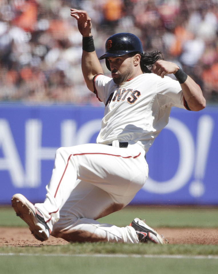 Photo - San Francisco Giants' Angel Pagan slides safely into third base advancing from second base after a throwing error by Milwaukee Brewers catcher Martin Maldonado during the third inning of a baseball game on Sunday, Aug. 31, 2014, in San Francisco. (AP Photo/Marcio Jose Sanchez)