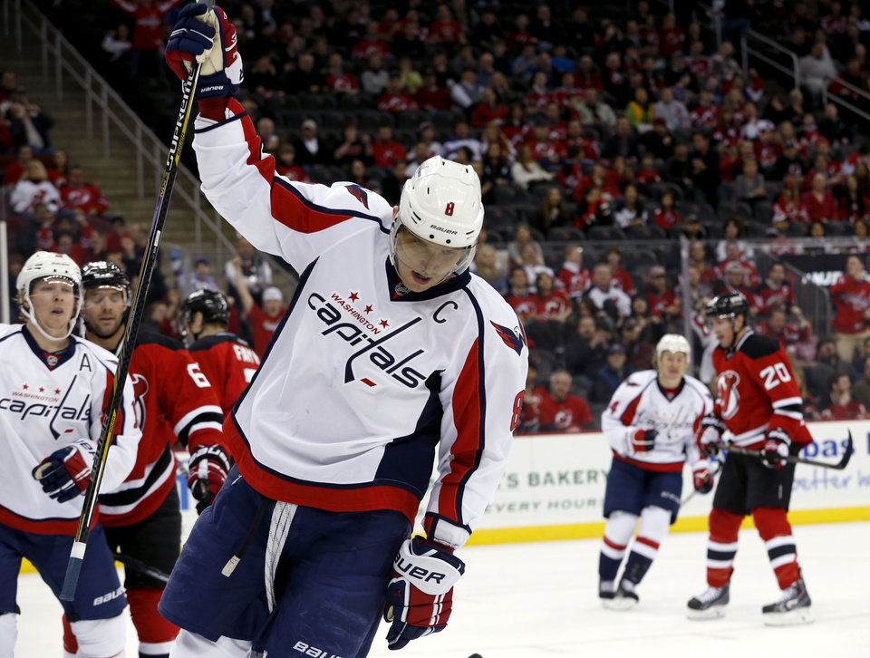 Photo - Washington Capitals right wing Alex Ovechkin, of Russia, celebrates after scoring a goal against the New Jersey Devils during the first period of an NHL hockey game, Friday, April 4, 2014, in Newark, N.J. (AP Photo/Julio Cortez)