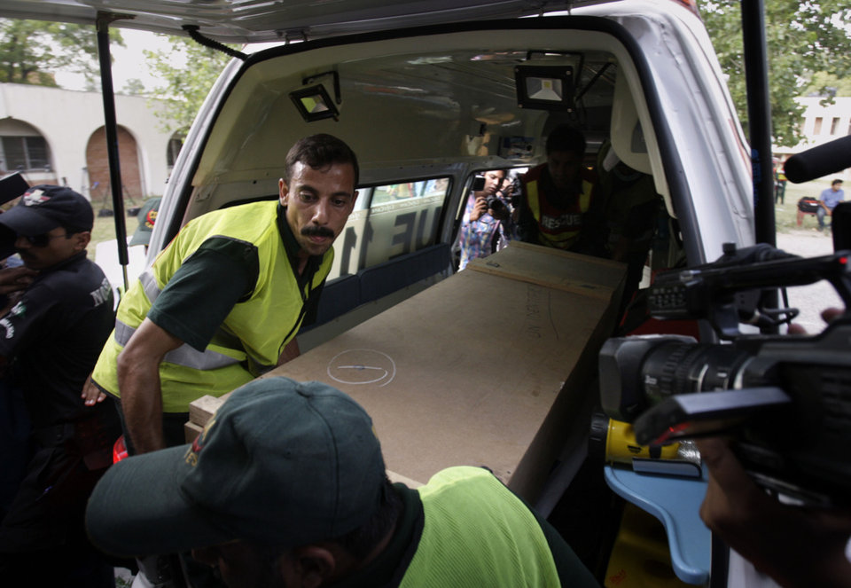 Photo - Pakistani rescue workers unload the casket of a foreign tourist who was killed by Islamic militants from an ambulance to shift in a morgue of local hospital in Islamabad, Pakistan, Sunday, June 23, 2013. Islamic militants wearing police uniforms shot to death foreign tourists and at least one Pakistani before dawn as they were visiting one of the world's highest mountains in a remote area of northern Pakistan that has been largely peaceful, officials said. (AP Photo/Anjum Naveed)