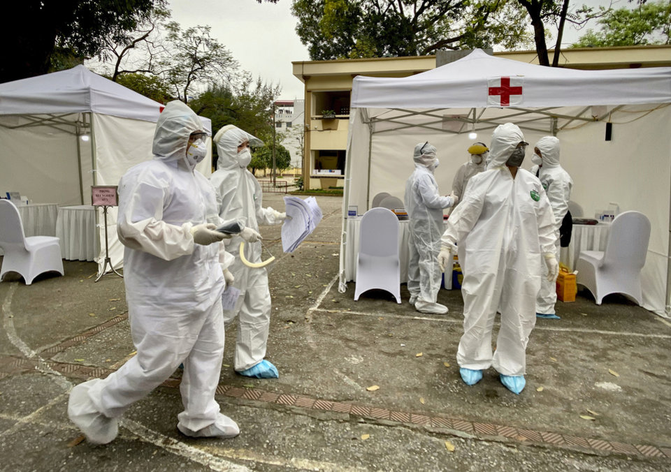 Photo -  Health workers walk through the grounds at a makeshift COVID-19 testing facility in Hanoi, Vietnam on Tuesday, Mar. 31, 2020. Vietnam has set up its first makeshift facilities for fast coronavirus testing in residential areas in an effort to detect early infections. (AP Photo/Hau Dinh)