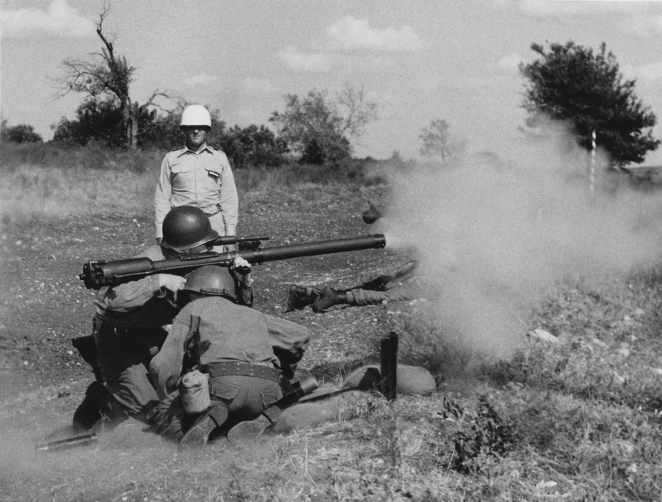 """Photo - This is no simulated action--the 57mm. recoilless rifle is blasting away.  The gunner is Spl. 3/c Charles Crites and his helper is Spl. 3/c Alvin Grantz.  Firing officer is Lieut. Donald Nave.  All are from company K, 179th infantry, Enid.  By Roy P. Stewart.  North Fort Hood, Aug. 10--Although to some of them this tent camp area has the real flavor and appearance of field training, Thunderbirds new to the 45th  Infantry division next week will learn what a real bivouac is, while to the larger group of experienced men it will be old hat.   With exception of a small fire and security guard, the entire division will take to the brush, going out Monday and returning Thursday evening.  The bivouac areas will be semi-tactical--if there is such a word--since kitchen and headquarters tents, and pup tents for personnel, will be dispersed and at least partially concealed.""""  Staff photo by George Tapscott, dated 08/08/1957.  Published in The Daily Oklahoman 08/11/1957."""