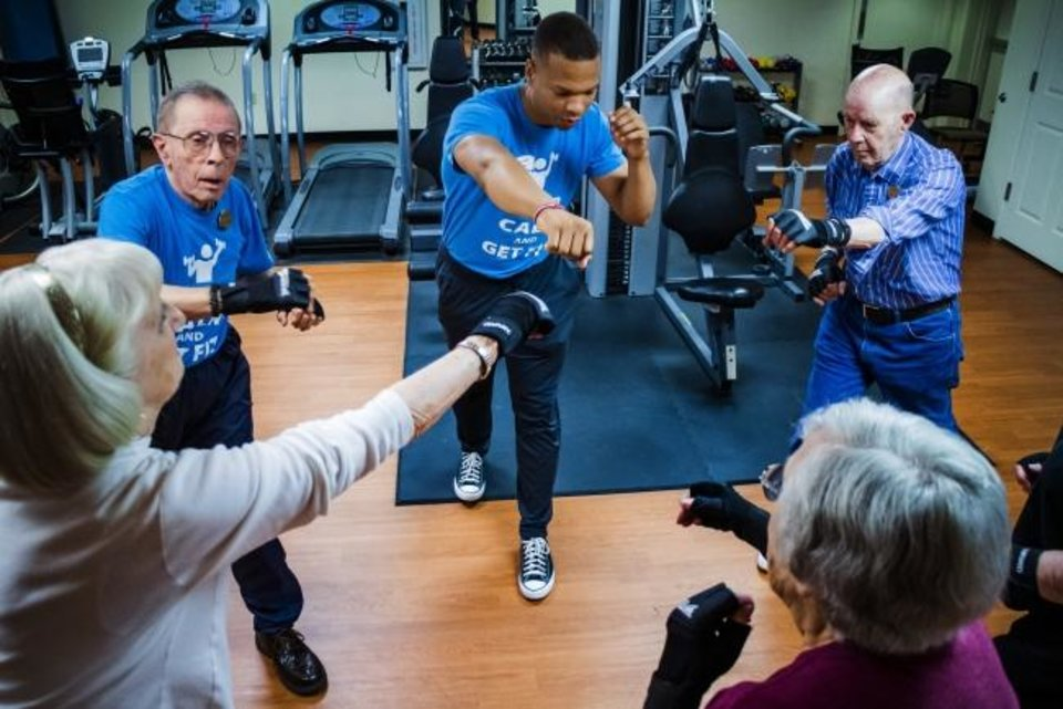 Photo -  Instructor Chris Coleman works out with participants in the Boxing for Better Balance class at Concordia Life Care Community in Oklahoma City. [Chris Landsberger/The Oklahoman]