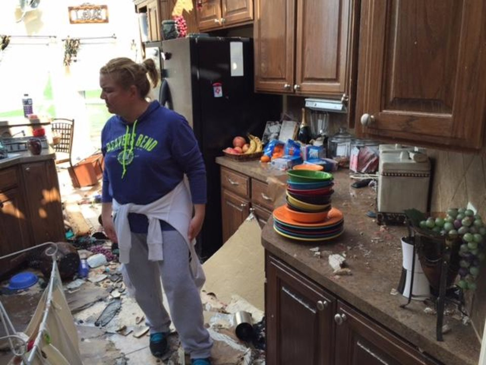 Photo - Jennifer Moon sorts through kitchen items to save in her home twice hit by Wednesday tornadoes. Photo by Steve Sisney