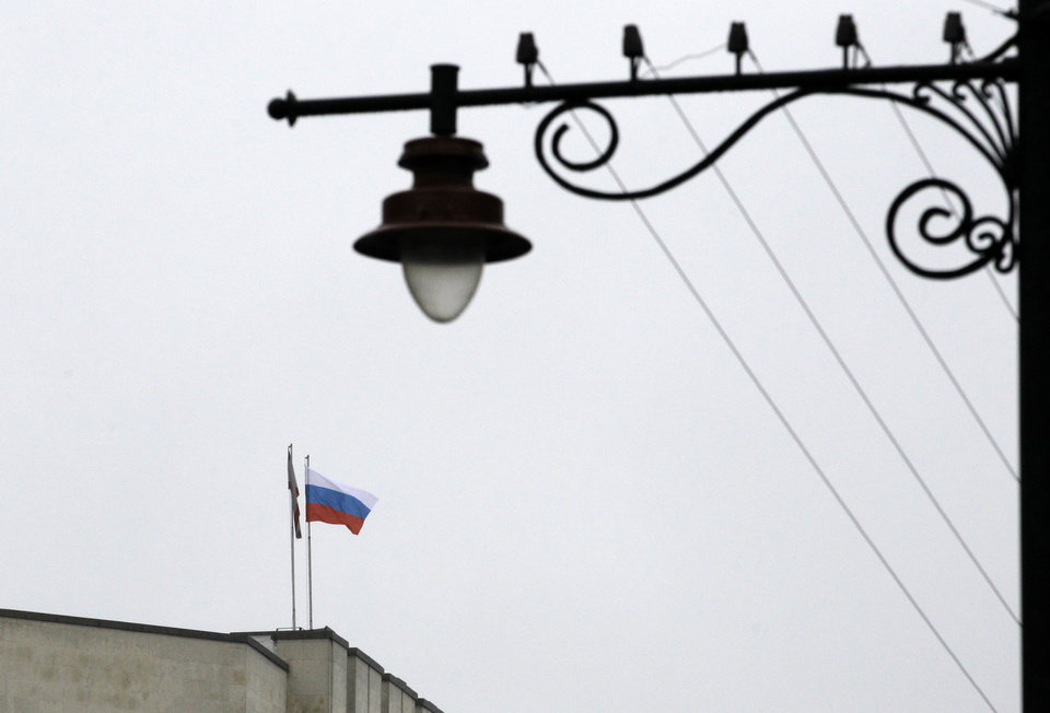 Photo - The Russian flag flies on a local government building in Simferopol, Crimea, Ukraine, Thursday, Feb. 27, 2014. Ukraine's acting interior minister says Interior Ministry troops and police have been put on high alert after dozens of men seized local government and legislature buildings in the Crimea region. The intruders raised a Russian flag over the parliament building in the regional capital, Simferopol, but didn't immediately voice any demands. (AP Photo/Darko Vojinovic)