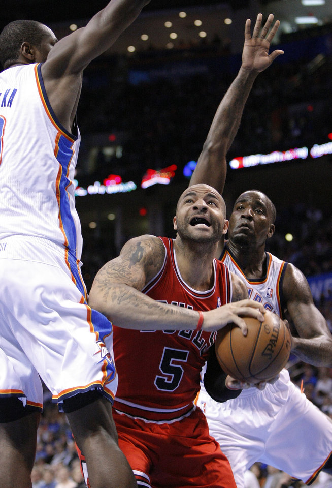 Chicago Bulls forward Carlos Boozer, center, eyes the basket between Oklahoma City Thunder defenders Serge Ibaka, left, and Kendrick Perkins during the second quarter of an NBA basketball game in Oklahoma City, Sunday, Feb. 24, 2013.  (AP Photo/Alonzo Adams)
