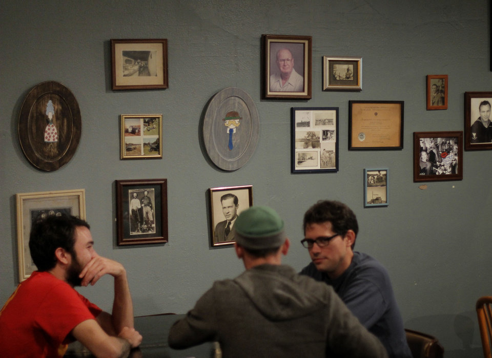 Photo - Patrons sit Thursday in front of a wall lined with photos at Grandad's Bar, 317 NW 23, part of the NW 23 Street revival. Photo by Doug Hoke, The Oklahoman  DOUG HOKE