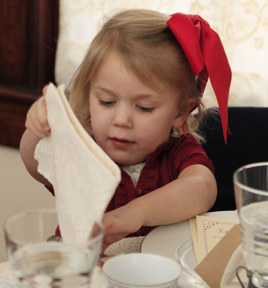 Photo -  Veronica Sorenson, 4, prepares her napkin during the Victorian Tea. [PHOTO BY PAUL HELLSTERN, THE OKLAHOMAN]