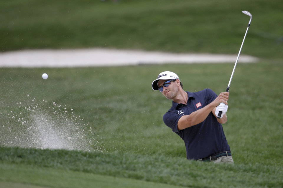 Photo - Adam Scott, of Australia, hits out of a bunker onto the 18th green during the first round of the Honda Classic golf tournament on Thursday, Feb. 27, 2014, in Palm Beach Gardens, Fla. (AP Photo/Lynne Sladky)