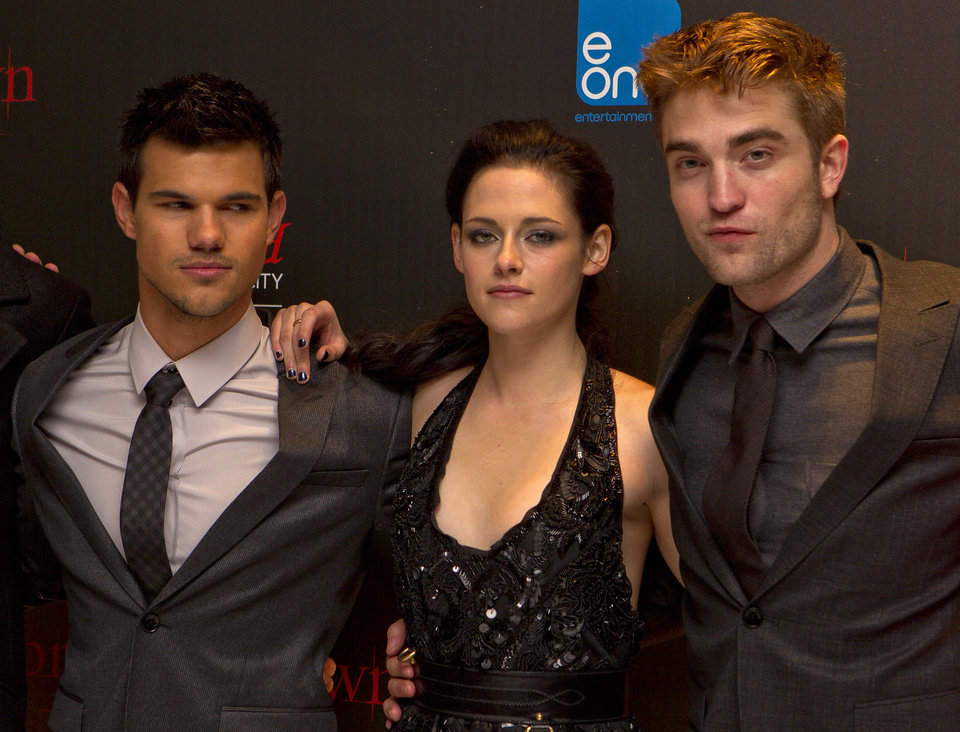 US actor Taylor Lautner, left, US actress Kristen Stewart, centre, and British actor Robert Pattinson pose for photographers at the UK film premiere of 'Twilight Breaking Dawn Part 1' at Westfield Stratford in east London, Wednesday, Nov. 16, 2011. (AP Photo/Joel Ryan) ORG XMIT: LENT124