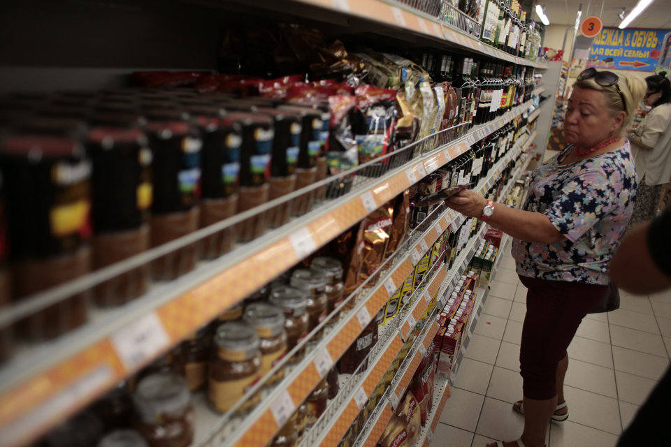 Photo - A woman choses sweets at a counter with imported food stuffs at a supermarket in downtown Moscow on Thursday, Aug. 7, 2014.The Russian government has banned all imports of meat, fish, milk and milk products and fruit and vegetables from the United States, the European Union, Australia, Canada and Norway, Prime Minister Dmitry Medvedev announced Thursday. The move was taken on orders from President Vladimir Putin in response to sanctions imposed on Russia by the West over the crisis in Ukraine. The ban has been introduced for one year.  (AP Photo/Ivan Sekretarev)