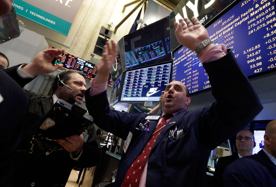Photo - Specialist Peter Giacchi, right, calls out prices at the closing bell on the floor of the New York Stock Exchange Thursday, Feb. 28, 2013.  The stock market pushed higher Thursday afternoon, sending the Dow tantalizingly close to a record high. (AP Photo/Richard Drew)
