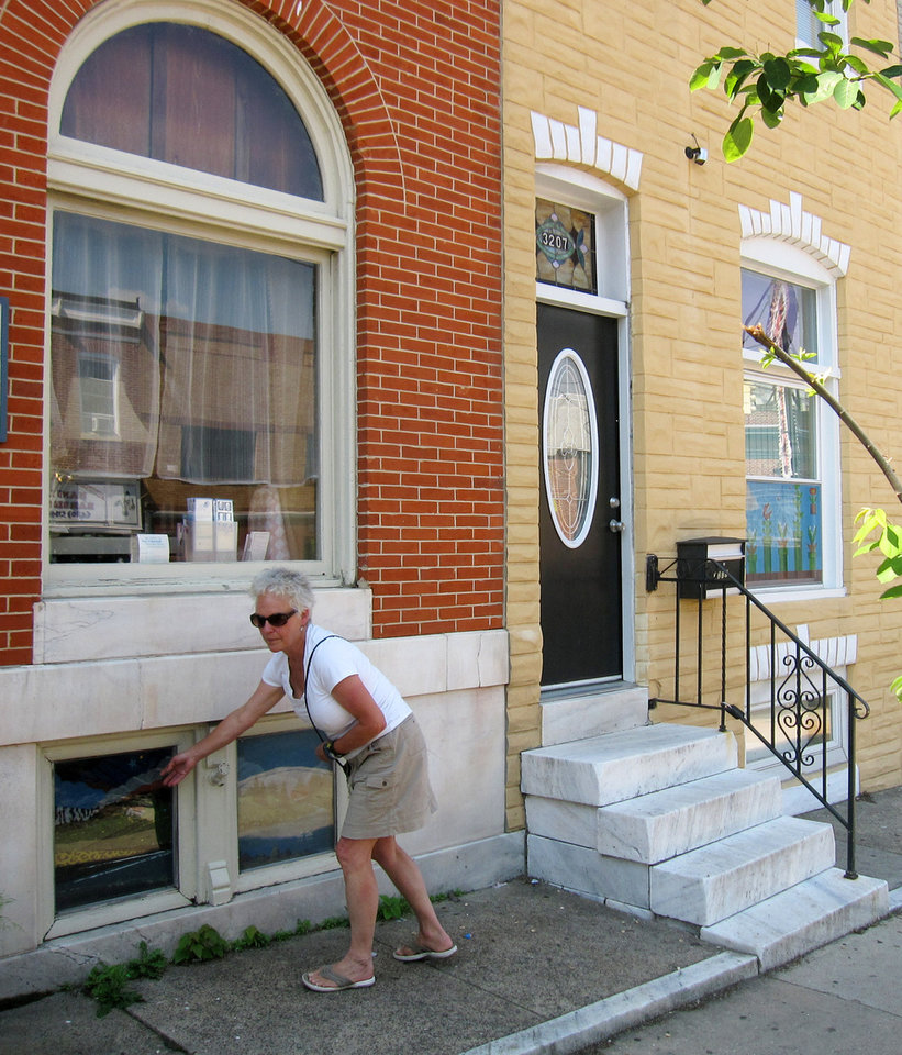 Photo - This June 8, 2014 shows artist Monica Broere gesturing to a painted window screen in the Highlandtown neighborhood of Baltimore. Painted screens were popular in the 20th century as a way to keep people walking by from looking inside the front windows of Baltimore's row houses. Broere and other artists are working to revitalize the urban folk tradition. (AP Photo/Beth J. Harpaz)