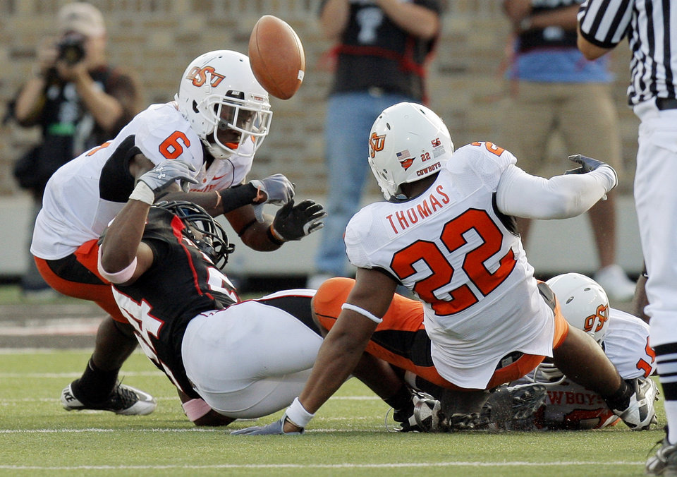 Photo - Texas Tech's Eric Stephens (24) fumbles the ball between OSU defenders Andrew McGee (6) and James Thomas (22) in the fourth quarter during the college football game between the Oklahoma State University Cowboys and Texas Tech University Red Raiders at Jones AT&T Stadium in Lubbock, Texas, Saturday, October 16, 2010.  The Cowboys recovered the fumble. OSU won, 34-17. Photo by Nate Billings, The Oklahoman