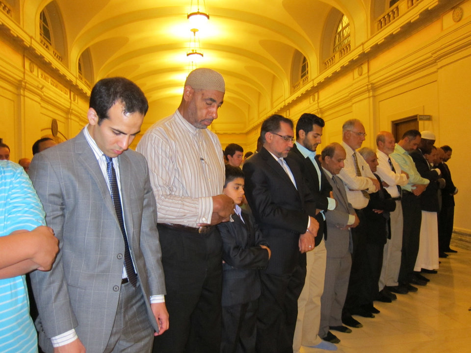 Photo - Muslim men participate in evening prayers after the Oklahoma State Capitol Interfaith Iftar Dinner program  Tuesday at the state Capitol. PHOTO BY CARLA HINTON, THE OKLAHOMAN   Carla Hinton - The Oklahoman