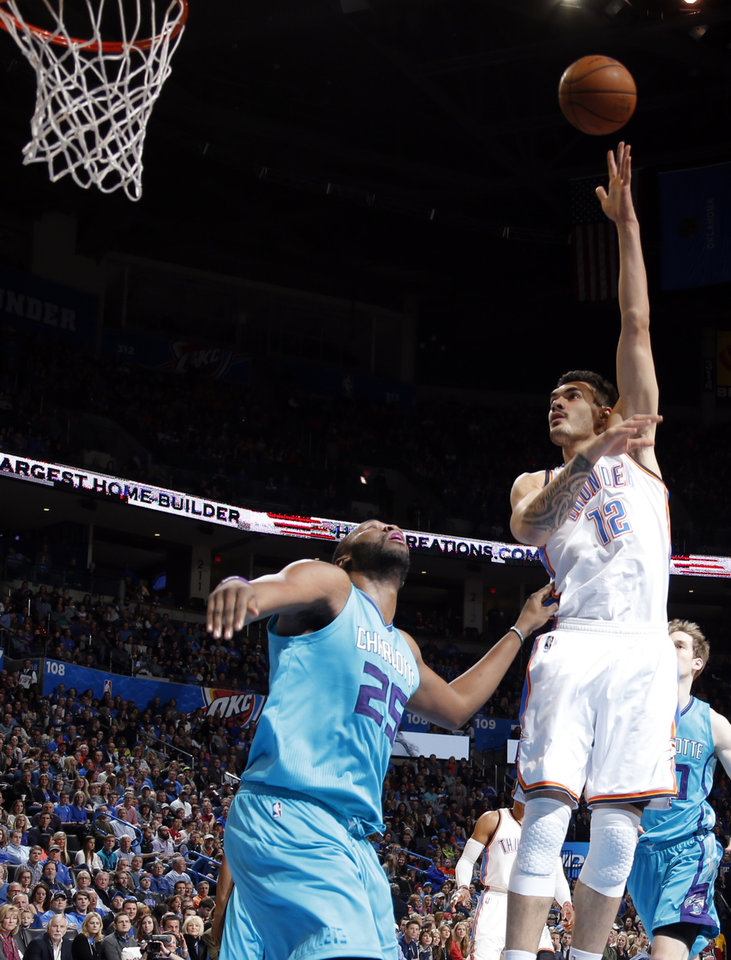 Photo - Oklahoma City's Steven Adams (12) shoots over Charlotte's Al Jefferson (25) during the NBA basketball game between the Oklahoma City Thunder and the Charlotte Hornets at the Chesapeake Energy Arena in Oklahoma City, Friday, Dec. 26, 2014. Photo by Sarah Phipps, The Oklahoman