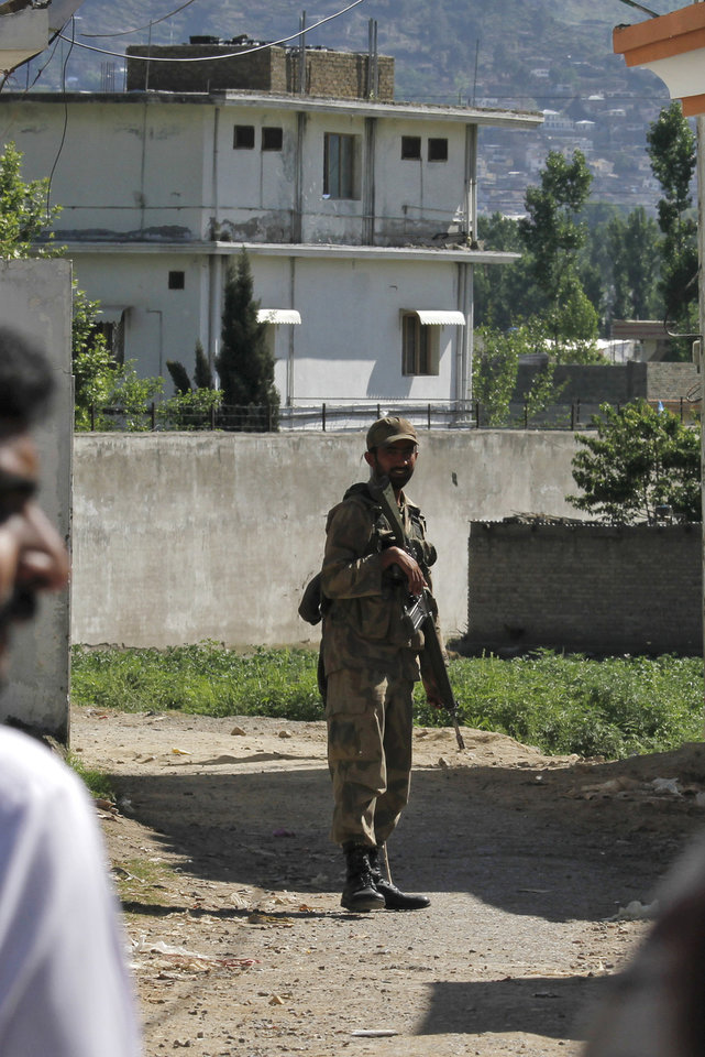 Photo -   FILE - In this this May 8, 2011, file photo, aPakistan army soldier secures a street close to the house, background, of former al-Qaida leader Osama. Pakistan on Saturday Feb 25 2012 began demolishing the three-story compound where Osama bin Laden lived for years and was killed by U.S. commandos last May, eliminating a concrete reminder of the painful and embarrassing chapter in the country's history. (AP Photo/Anjum Naveed, File)