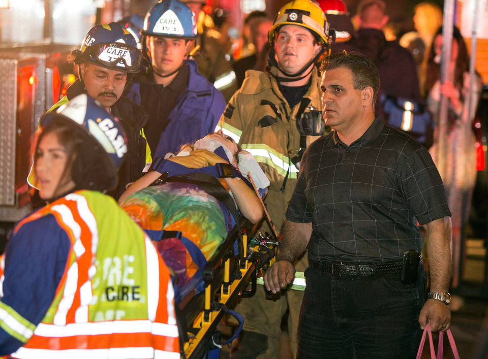 Photo - A parent accompanies his injured daughter as firefighters carry her from Servite High School after a stage collapsed during a student event at the high school in Anaheim, Calif., Saturday, March 8, 2014. Authorities said 30-40 people were rushed to hospitals with mainly minor injuries. (AP Photo/Kevin Warn)