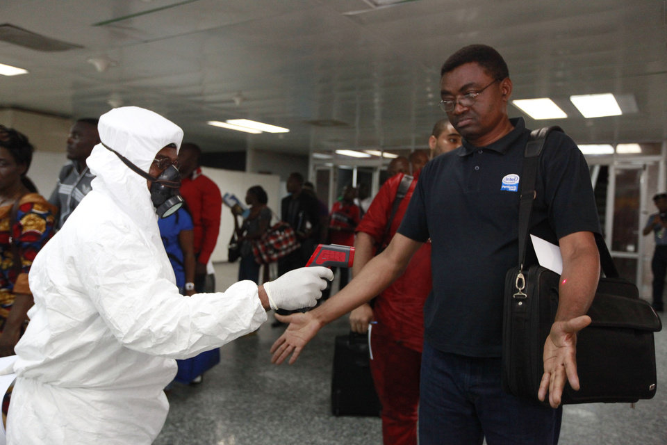 Photo - A Nigerian port health official uses a thermometer on a passenger at the arrivals hall of Murtala Muhammed International Airport in Lagos, Nigeria,  Wednesday, Aug. 6, 2014. A Nigerian nurse who treated a man with Ebola is now dead and five others are sick with one of the world's most virulent diseases, authorities said Wednesday as the death toll rose to at least 932 people in four West African countries. (AP Photo/Sunday Alamba)