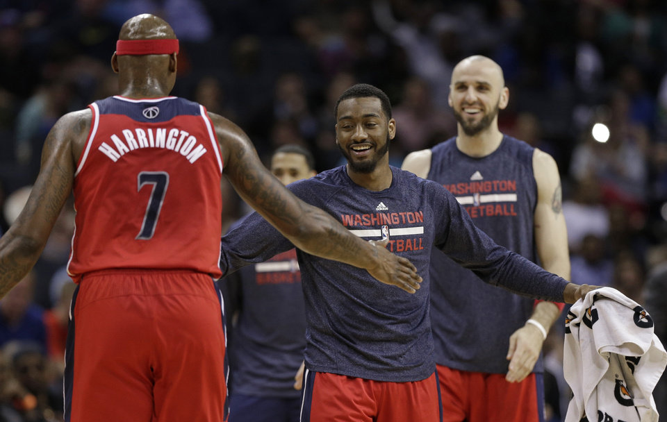 Photo - Washington Wizards' John Wall, right, congratulates Al Harrington, left, during a timeout in the first half of an NBA basketball game against the Charlotte Bobcats in Charlotte, N.C., Monday, March 31, 2014. (AP Photo/Chuck Burton)